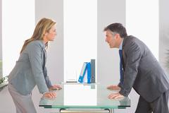 Two angry businesspeople arguing on each side of a desk Stock Photos