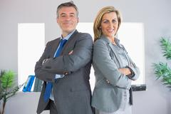 Stock Photo of Two happy businesspeople looking at camera standing back to back