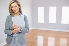 Satisfied realtor standing in a room holding documents - stock photo
