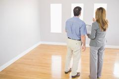 Blonde realtor showing a room to a potential buyer - stock photo