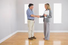 Serious realtor shaking the hand of her buyer - stock photo