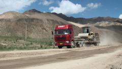 Chinese truck with excavator on Kyrgyzstan road, development assistance abroad Stock Footage
