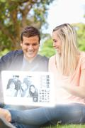 Smiling young couple watching photos on digital interface - stock photo