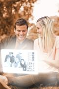 Happy young couple watching photos on digital interface - stock photo