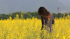 Young woman with long hair in the wind walk in flourish yellow field Stock Footage