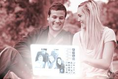 Cheerful young couple watching photos together on digital interface Stock Photos