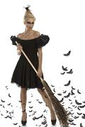 Sexy girl in halloween suit with besom in all hands Stock Photos
