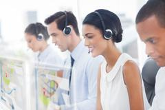 Call center employees at work on futuristic hologram interfaces - stock photo