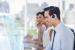 Call center employees at work on futuristic interfaces showing maps - stock photo