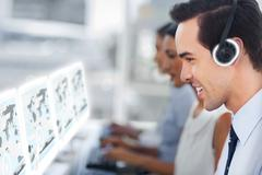 Call center staff at work on futuristic interfaces showing maps - stock photo