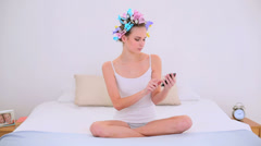Young model in hair rollers sending a text on her bed Stock Footage