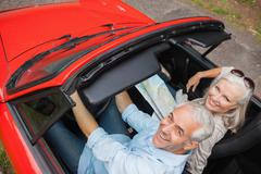 High angle view of cheerful mature man having a ride with his wife - stock photo