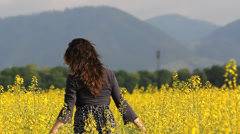 Beautiful scenery, free young lady walk and touch yellow flower  Stock Footage
