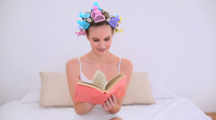 Young model in hair rollers reading a book on her bed Stock Footage