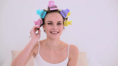 Young model in hair rollers brushing her eyebrows Stock Footage