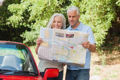 Stock Photo of Smiling mature couple reading map