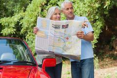 Stock Photo of Smiling mature couple reading map looking for direction