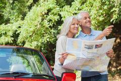 Stock Photo of Cheerful mature couple reading map looking for direction