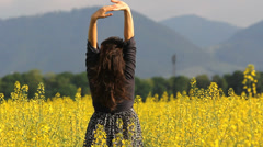 Young lady relax in nature, rise up hands in yellow flower field Stock Footage