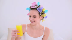 Young model in hair rollers drinking glass of orange juice Stock Footage