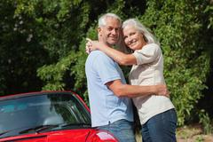 Smiling mature couple hugging against their red cabriolet - stock photo