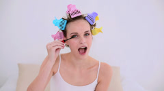 Young model in hair rollers putting on mascara Stock Footage