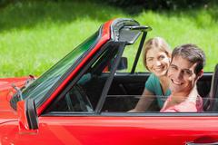 Cheerful young couple having a ride in red cabriolet - stock photo