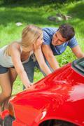 Happy couple pushing their broken down car Stock Photos