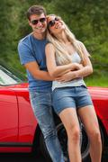 Loving couple hugging and leaning against cabriolet - stock photo