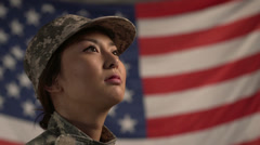 Asian female soldier in front of American flag Stock Footage