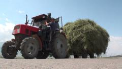 Tractor with lots of hay on a trailer in Kyrgyzstan Stock Footage