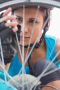 Focused woman adjusting her spokes on bike wheel Stock Photos