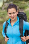 Smiling female hiker with backpack looking at camera - stock photo