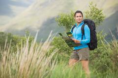 Attractive female hiker with backpack holding a map - stock photo