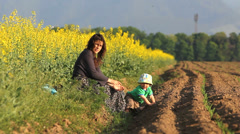 Young mother sit on spring soil near rape field in bloom, baby try to lift up  Stock Footage