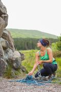 Pretty rock climber looking up at her challenge - stock photo