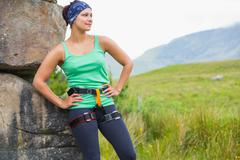 Stock Photo of Pretty female rock climber leaning on rock face