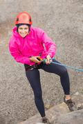 Happy girl abseiling down rock face Stock Photos