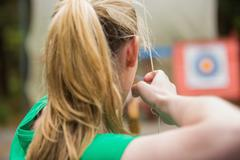 Rear view of blonde about to shoot arrow - stock photo