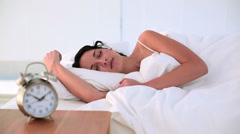Brunette being woken by her alarm clock in bed Stock Footage