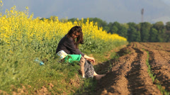 Young mother sit on spring ground near a rape field in bloom, little baby raise  Stock Footage