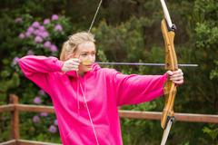 Concentrating blonde practicing archery - stock photo