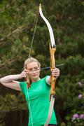 Concentrating blonde woman practicing archery - stock photo