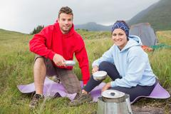 Couple cooking outside on camping trip smiling at camera - stock photo
