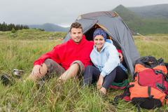 Couple on camping trip smiling at camera - stock photo