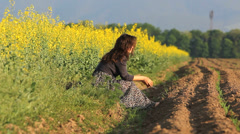 Single girl sit on spring ground near rape field in bloom admire nature Stock Footage