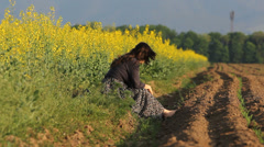 Young lady with long hair sit barefoot on spring ground play with a flower Stock Footage