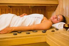 Peaceful brunette woman lying in a sauna - stock photo