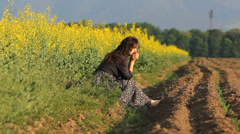 Worried woman  sit alone on ground, flourish rape field and fertile soil Stock Footage