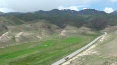 Chinese cargo truck drives through Kyrgyzstan mountains Stock Footage